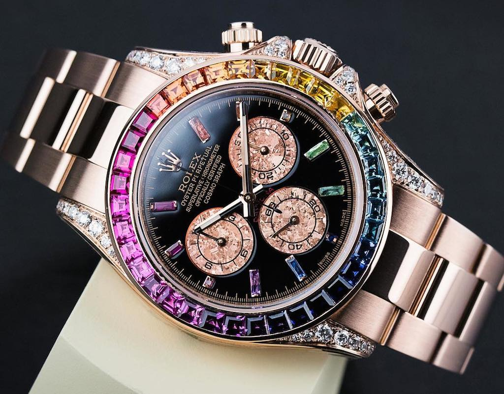 Everose Rolex Daytona with a custom bezel set with gems in rainbow hues and a custom black dial with sapphires, rubies and emeralds as hour markers.